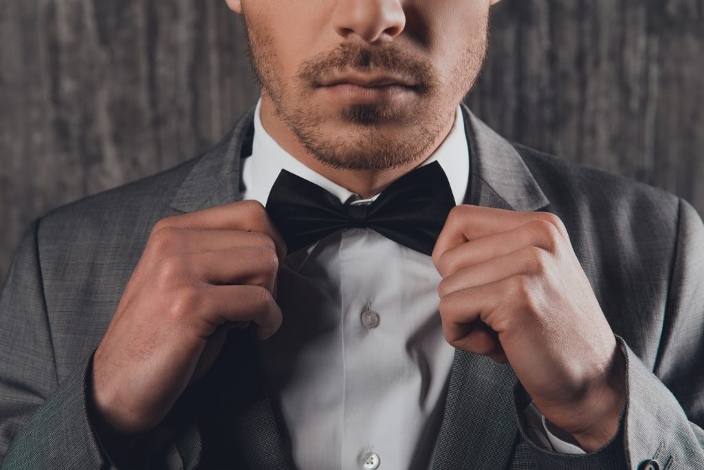 fastening a bow-tie on his shirt